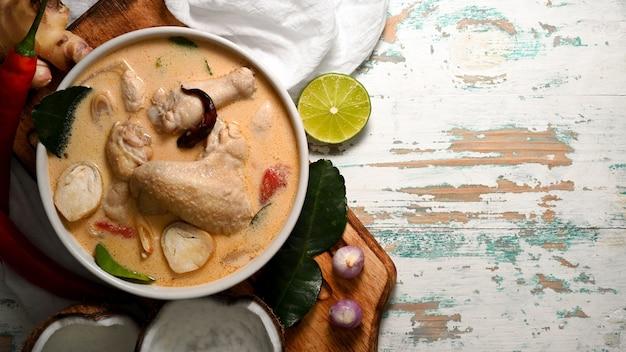 Draufsicht von tom kha gai, kokosmilchsuppe mit huhn, thailändisches essen auf holztisch mit kopienraum