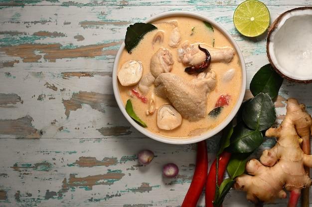 Draufsicht von tom kha gai, kokosmilchsuppe mit huhn, thailändisches essen auf holztisch mit zutaten und kopienraum