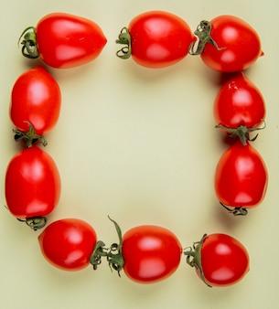 Draufsicht von tomaten, die in quadratischer form auf gelber oberfläche mit kopierraum gesetzt werden