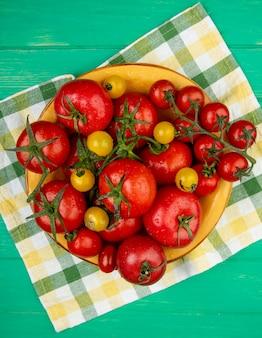 Draufsicht von tomaten in der schüssel auf stoff auf grüner oberfläche