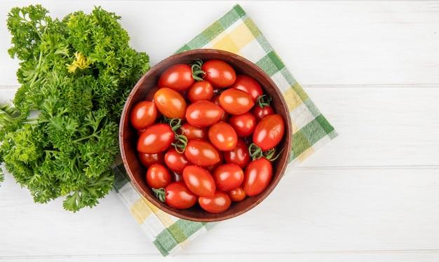 Draufsicht von tomaten in der schüssel mit chinesischem koriander auf stoff und holzoberfläche mit kopienraum