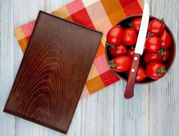 Draufsicht von tomaten mit messer in schüssel und leerem tablett auf stoff auf holzoberfläche