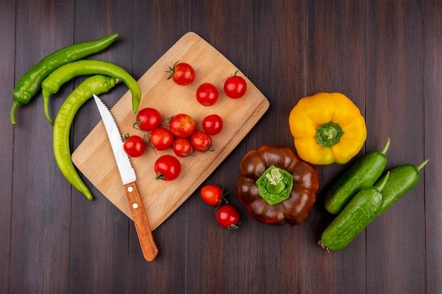 Draufsicht von tomaten und messer auf schneidebrett mit paprika und gurken herum auf holzoberfläche