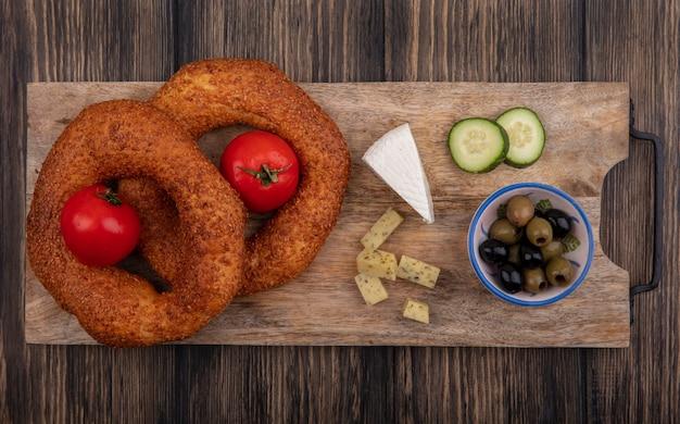 Draufsicht von türkischen bagels auf einem hölzernen küchenbrett mit oliven auf einer schüssel mit gehackten scheiben von gurke und käse auf einem hölzernen hintergrund