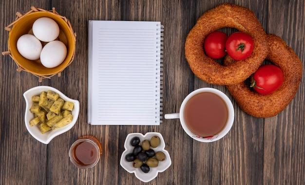 Draufsicht von türkischen sesambagels mit eiern auf einem eimer mit oliven auf einer schüssel und einer tasse tee auf einem hölzernen hintergrund mit kopienraum