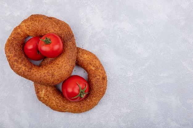 Draufsicht von türkischen sesambagels mit frischen tomaten auf einem weißen hintergrund mit kopienraum