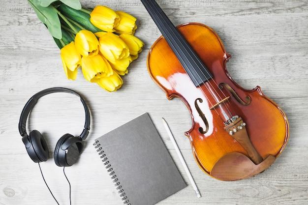 Draufsicht von tulpen; tagebuch; bleistift und violine auf hölzernem hintergrund