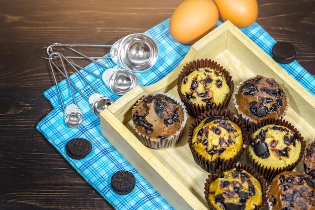 Draufsicht von vanila, kaffee, schokoladenmuffins im halter des kleinen kuchens auf serviette, hölzernes backgrou