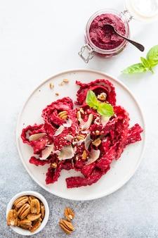 Draufsicht von vegetarischen mafaldine teigwaren mit pestosoße der roten rübe