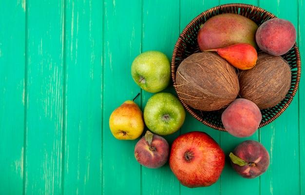 Draufsicht von verschiedenen früchten wie kokosnussapfelpfirsichbirne auf eimer auf grün
