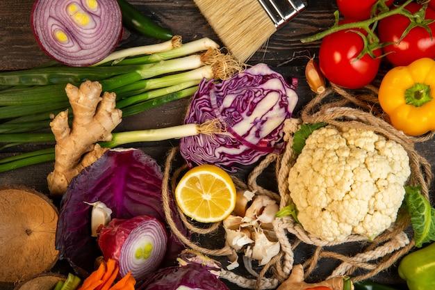 Draufsicht von verschiedenen gemüse rotkohl blumenkohl frühlingszwiebel zitrone und tomaten auf