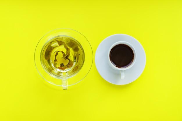Draufsicht von verschiedenen getränken - trinkbecher kaffee und grüner tee auf gelbem backgeound.