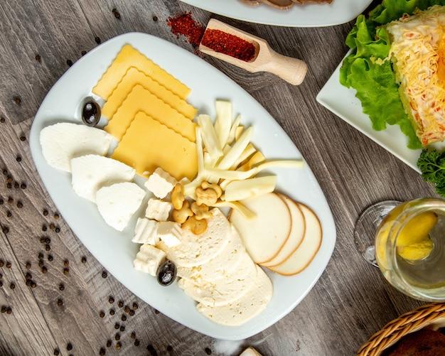 Draufsicht von verschiedenen käsesorten auf einem weißen teller auf tisch