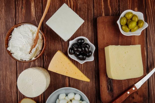 Draufsicht von verschiedenen käsesorten und hüttenkäse in einer schüssel mit eingelegten oliven auf rustikalem tisch