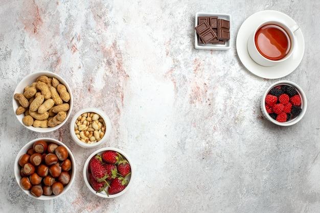 Draufsicht von verschiedenen nüssen haselnüssen erdnüssen und tasse tee auf weißer oberfläche