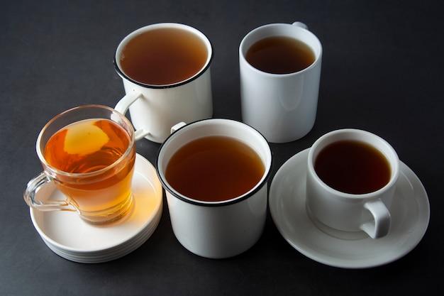 Draufsicht von verschiedenen schalen, becher mit heißem tee trinken auf dunkelheit, copyspace. teezeit oder teepause. herbstgetränk. getontes bild mit teetassen.