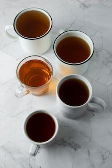Draufsicht von verschiedenen schalen, becher mit heißem tee trinken auf licht, copyspace. teezeit oder teepause. herbstgetränk. getontes bild mit teetassen.