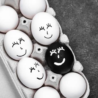 Draufsicht von vielen verschiedenfarbigen eiern mit gesichtern für bewegung der schwarzen lebensmaterie