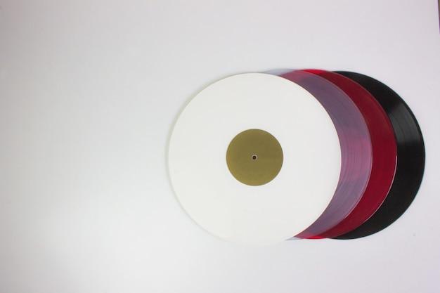Draufsicht von vier vinyls, schwarz, rot, blau und weiß, auf weiß.