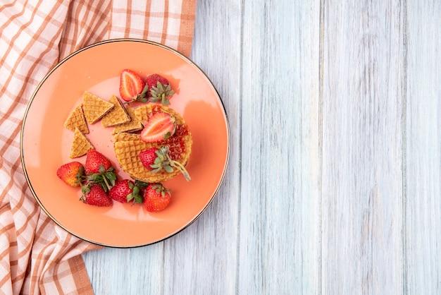 Draufsicht von waffelkeksen mit erdbeeren in platte auf kariertem stoff und holzoberfläche