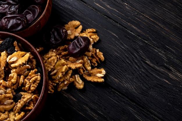 Draufsicht von walnüssen in einer schüssel und süßen getrockneten dattelfrüchten auf holz