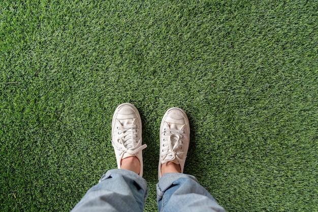 Draufsicht von weiblichen füßen mit den turnschuhen, die auf grünem künstlichem gras stehen