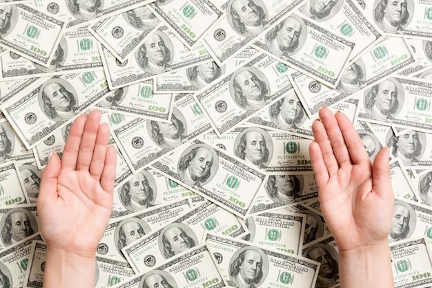 Draufsicht von weiblichen händen auf dollarhintergrund