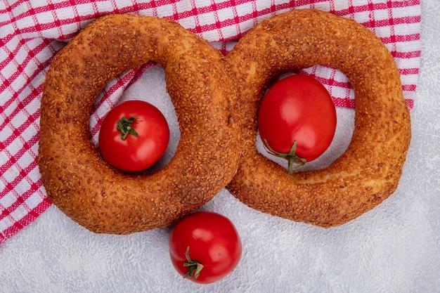 Draufsicht von weichen traditionellen türkischen bagels mit frischen tomaten auf einem roten karierten tuch auf einem weißen hintergrund