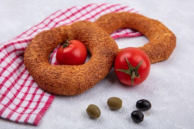 Draufsicht von weichen traditionellen türkischen bagels mit frischen tomaten und oliven auf einem roten karierten tuch auf einem weißen hintergrund