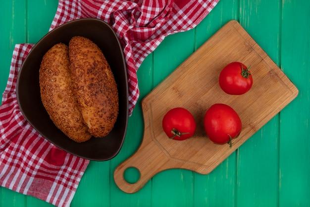 Draufsicht von weichen und sesamfrikadellen auf einer schüssel mit frischen tomaten auf einem hölzernen küchenbrett auf einem roten karierten tuch auf einem grünen hölzernen hintergrund