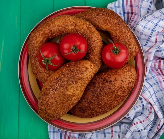 Draufsicht von weichen und sesamfrikadellen auf einer schüssel mit frischen tomaten auf einem stoff auf einem grünen hölzernen hintergrund