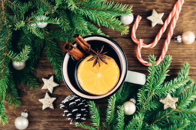 Draufsicht von weihnachten und neujahr trinken heißen wein, glühwein, punsch oder tee auf holztisch neben grünem baum und weihnachtszuckerstangen.