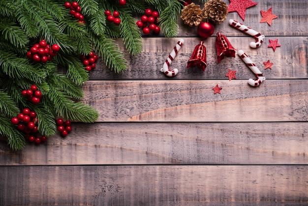 Draufsicht von weihnachtsfichtenzweigen, von kiefernkegeln, von roten beeren und von glocke auf alter hölzerner rückseite