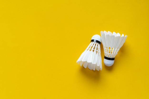 Draufsicht von weißen federbällen auf gelbem farbhintergrund