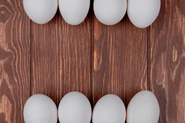 Draufsicht von weißen frischen hühnereiern auf einem hölzernen hintergrund mit kopienraum