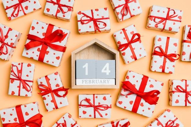 Draufsicht von weißen geschenkboxen mit herzen und hölzernem kalender