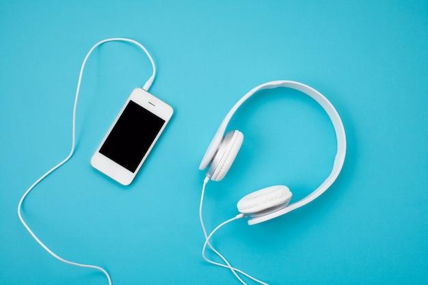 Draufsicht von weißen kopfhörern mit smartphone auf blauem hintergrund. online-musikkonzept