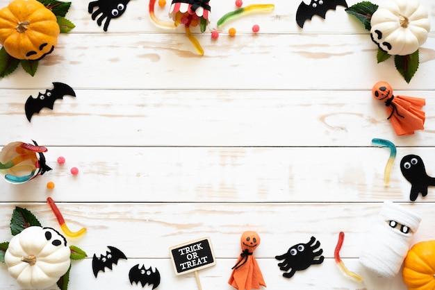 Draufsicht von weißen und gelben geistkürbisen, halloween-handwerk auf weißem hölzernem hintergrund
