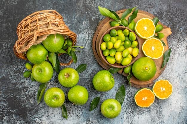 Draufsicht von weitem äpfel grüne äpfel mit blättern im korb zitrusfrüchte auf dem brett