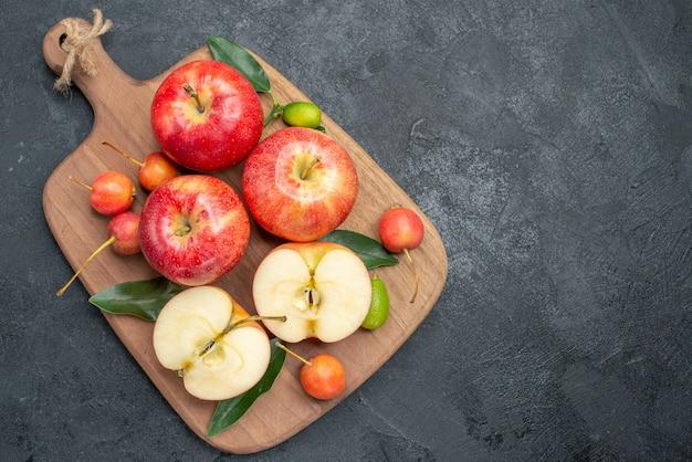Draufsicht von weitem äpfel kirschen äpfel zitrusfrüchte auf dem schneidebrett