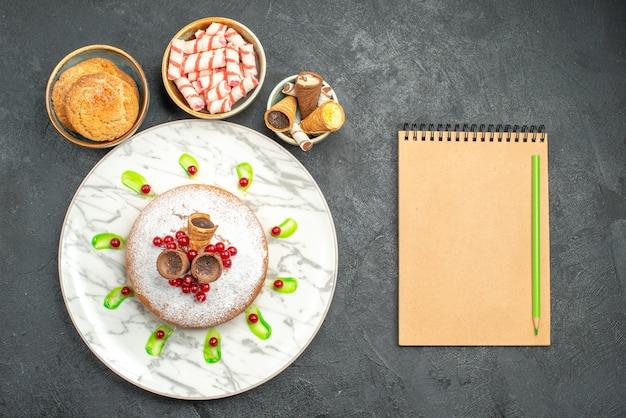 Draufsicht von weitem ein kuchen ein appetitlicher kuchen mit beerenplätzchen bonbons waffeln notizbuchstift