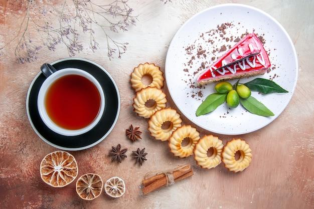 Draufsicht von weitem eine kuchenplätzchenplatte eines appetitlichen kuchens eine tasse tee sternanis zitrone
