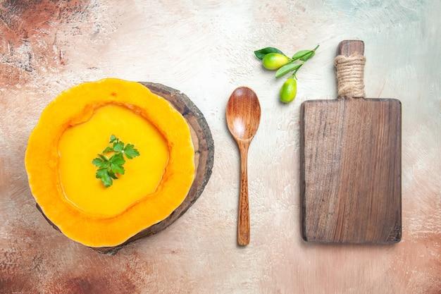 Draufsicht von weitem eine suppe kürbissuppe auf dem brett neben dem löffel das schneidebrett