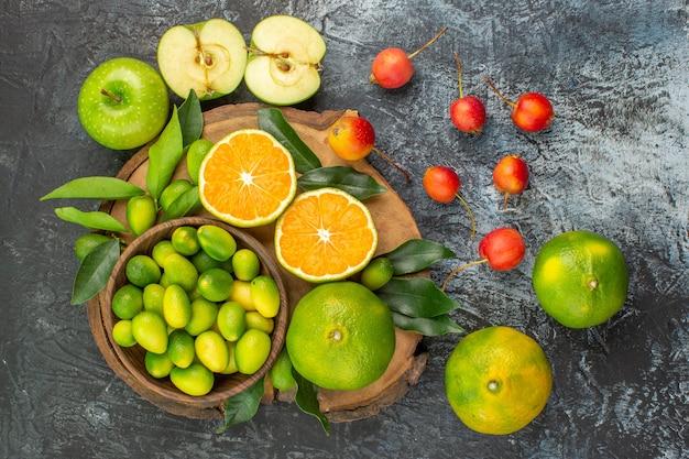 Draufsicht von weitem früchte kirschen äpfel zitrusfrüchte auf dem schneidebrett