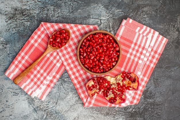 Draufsicht von weitem granatapfelschale von granatapfelkernen geschälten granatapfellöffel auf der tischdecke