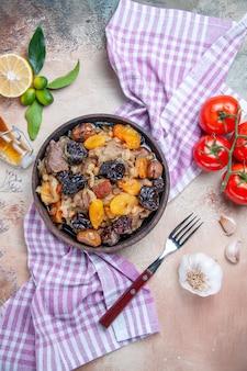 Draufsicht von weitem pilaw pilaw auf der tischdecke tomaten knoblauch zitronenöl gabel