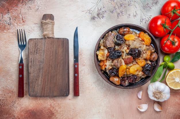 Draufsicht von weitem pilaw tomaten zitronen knoblauch schüssel pilaw das schneidebrett messer gabel