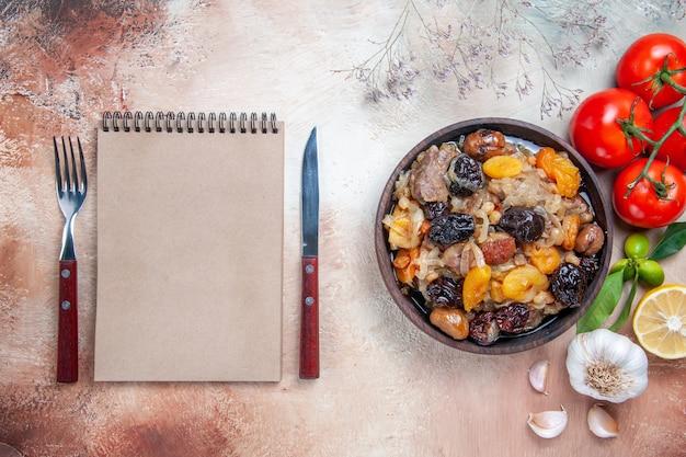 Draufsicht von weitem pilaw tomaten zitronen knoblauch schüssel pilaw notebook messer gabel