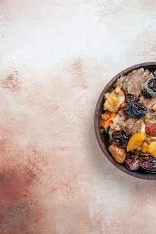 Draufsicht von weitem pilawreis mit kastanien getrockneten früchten auf dem tisch