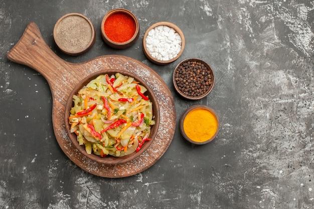 Draufsicht von weitem salat ein appetitlicher gemüsesalat auf dem brett bunte gewürze